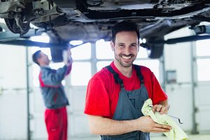 Auto Mechanic standing beneath a raised car, smiling at the camera