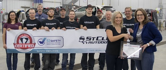 ST Claude Autobody staff holding SAFE Work Certification banner.